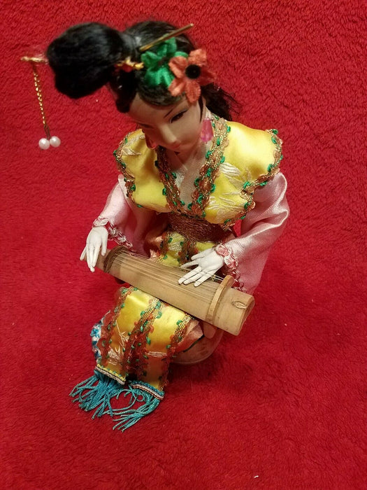 Asian Doll in Traditional Garb, Sitting on a Barrel and Playing a Lap Harp