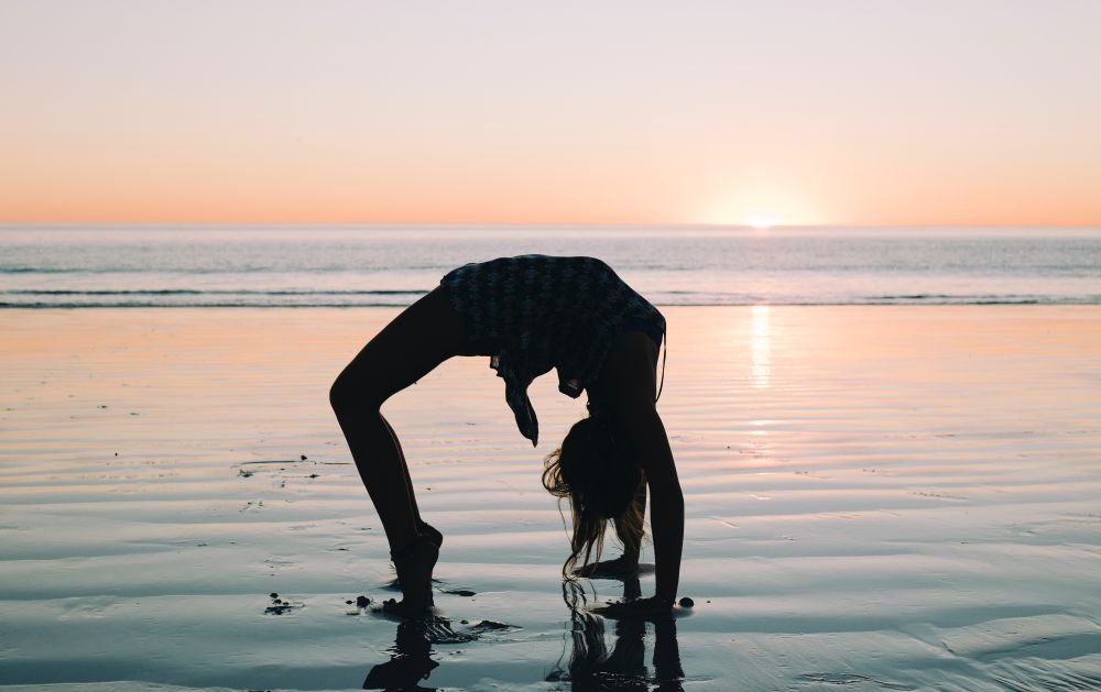 yoga wheel pose sunset