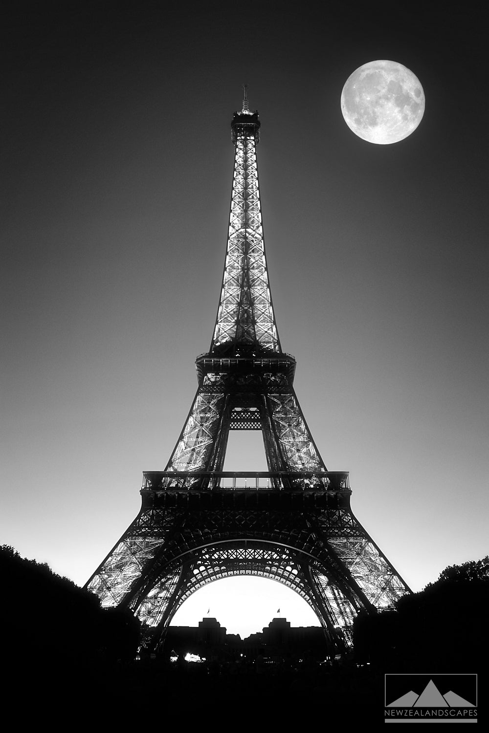 Black and white photo of the Eiffel Tower, Paris at night with full moon in the sky.