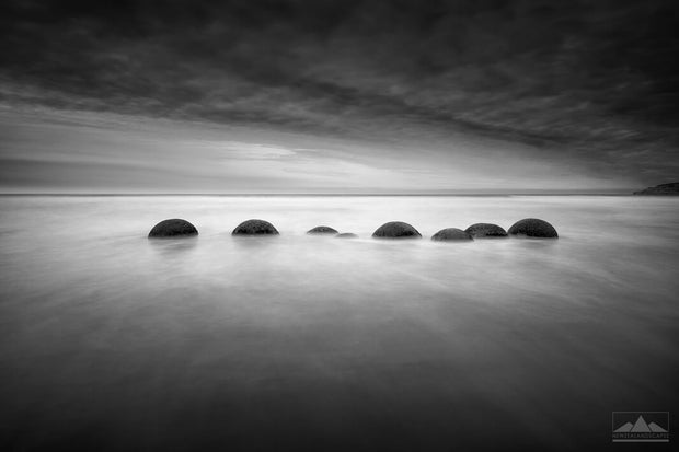 Black and white long exposure photo of eight Moeraki Boulders in a row.