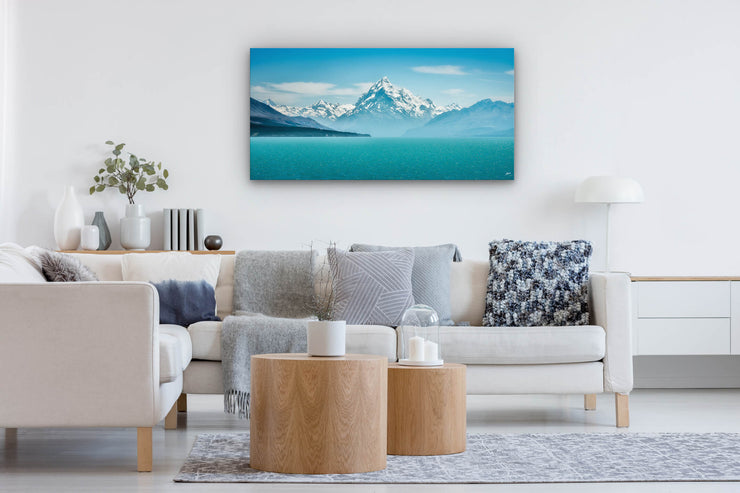 Blue toned photo print of Aoraki Mt Cook on the wall of a lounge with neutral decor.