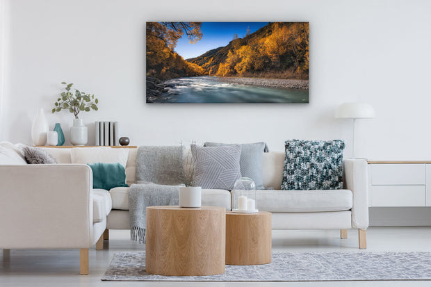Panoramic photo hung on a lounge wall, showing the Arrow River in Arrowtown during autumn.