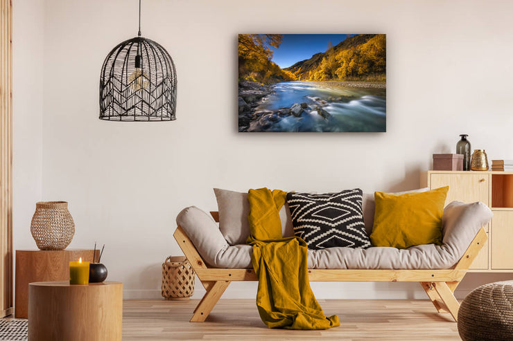 Sitting room with photo print of Arrowtown, Otago during autumn. Bright blue sky complements the yellow trees.
