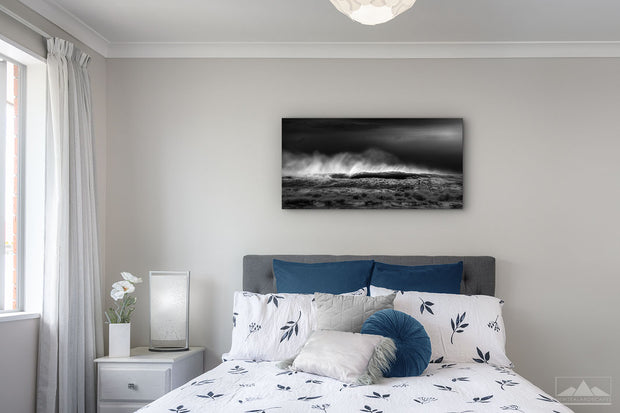 Fine art panoramic black and white canvas of crashing waves on the wall of a bedroom