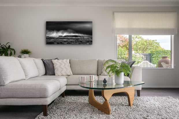 Fine art panoramic black and white canvas of crashing waves on the wall of a modern living room