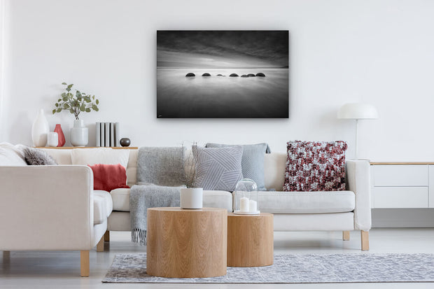 Canvas print on a modern lounge wall of black and white Moeraki boulders