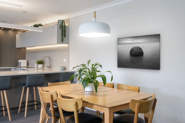 Canvas photo print of a Moeraki boulder displayed on a dining room wall.