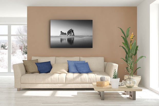 Fine art black and white canvas print showing the Archway Island rocks at Wharariki Beach, displayed on a lounge room wall