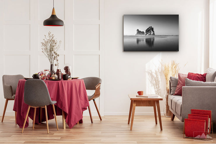 Fine art black and white photo print showing the Archway Island rocks at Wharariki Beach, displayed on a dining room wall