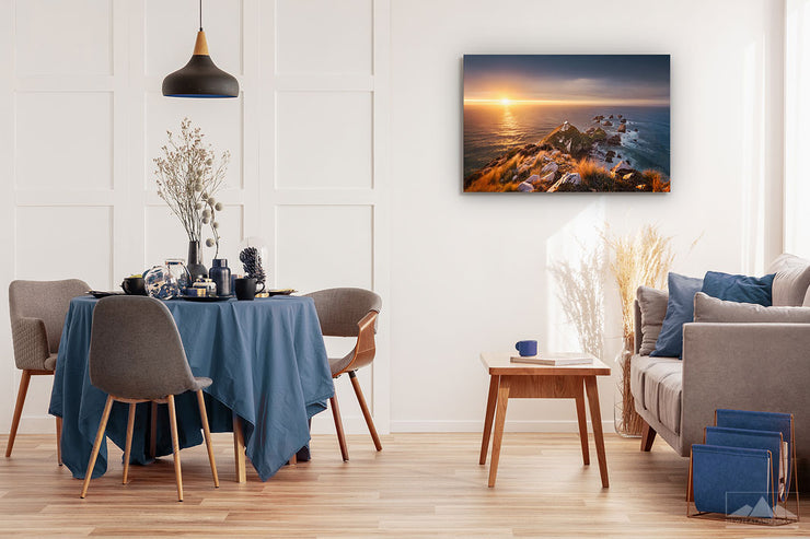 Canvas wall art photo on a dining room wall of the sunrise at Nugget Point lighthouse in Otago, New Zealand
