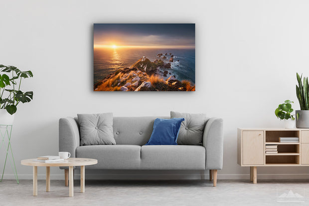 Canvas wall art photo on a lounge wall of the sunrise at Nugget Point lighthouse in Otago, New Zealand