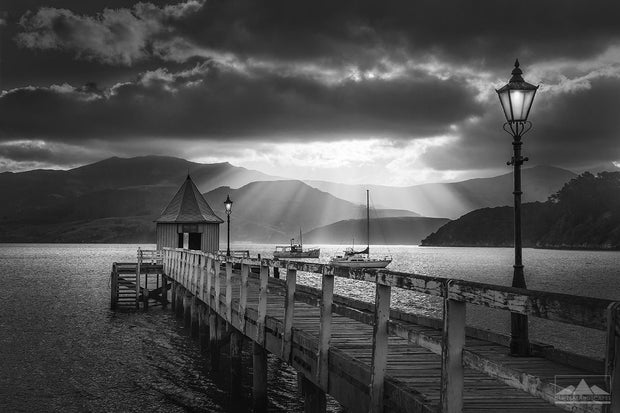 Photo in black and white of Akaroa jetty, lamp and small house at sunset with sunrays beaming down over the hills