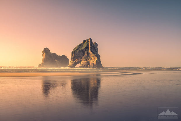 Warm sunset photo of the Archway Island rock stack reflected onto the sand at Wharariki Beach.