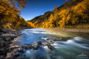 A long exposure photo of the Arrow River and golden autumn leaves of the trees in Arrowtown, Otago.