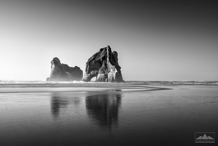 Black and white photo of huge rocks called Archway Islands, in the sea at Wharariki Beach in Tasman, New Zealand