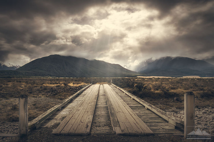 Old wooden bridge in the foreground leading towards mountains. Sunrays coming through the stormy clouds above.