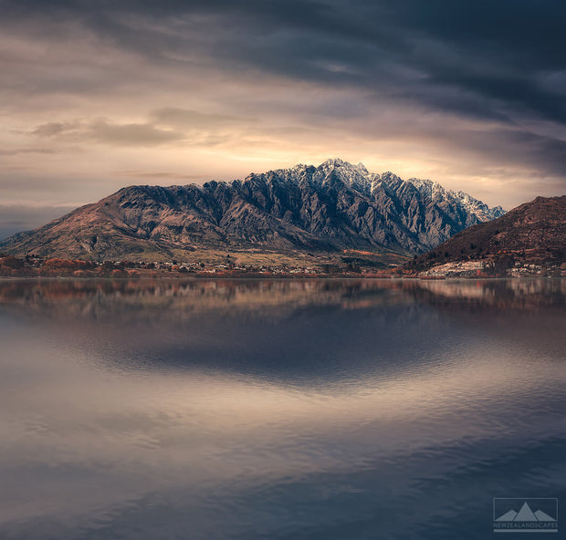 Landscape photo of The Remarkables snow capped mountain range near Queenstown with the lake in the foreground and sun rising behind clouds in the background