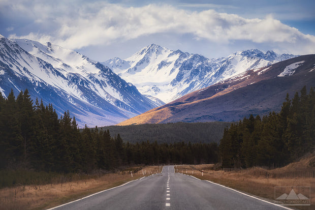 New Zealand country road leading to snowy mountains