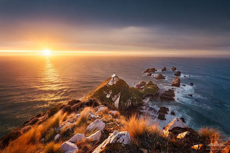 Photo of the sun rising across the ocean at the Nugget Point lighthouse, Otago, New Zealand
