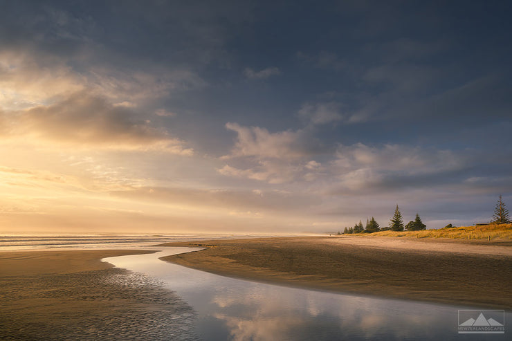 Landscape photograph of Waihi Beach at sunrise with the clouds reflected in the stream in the foreground