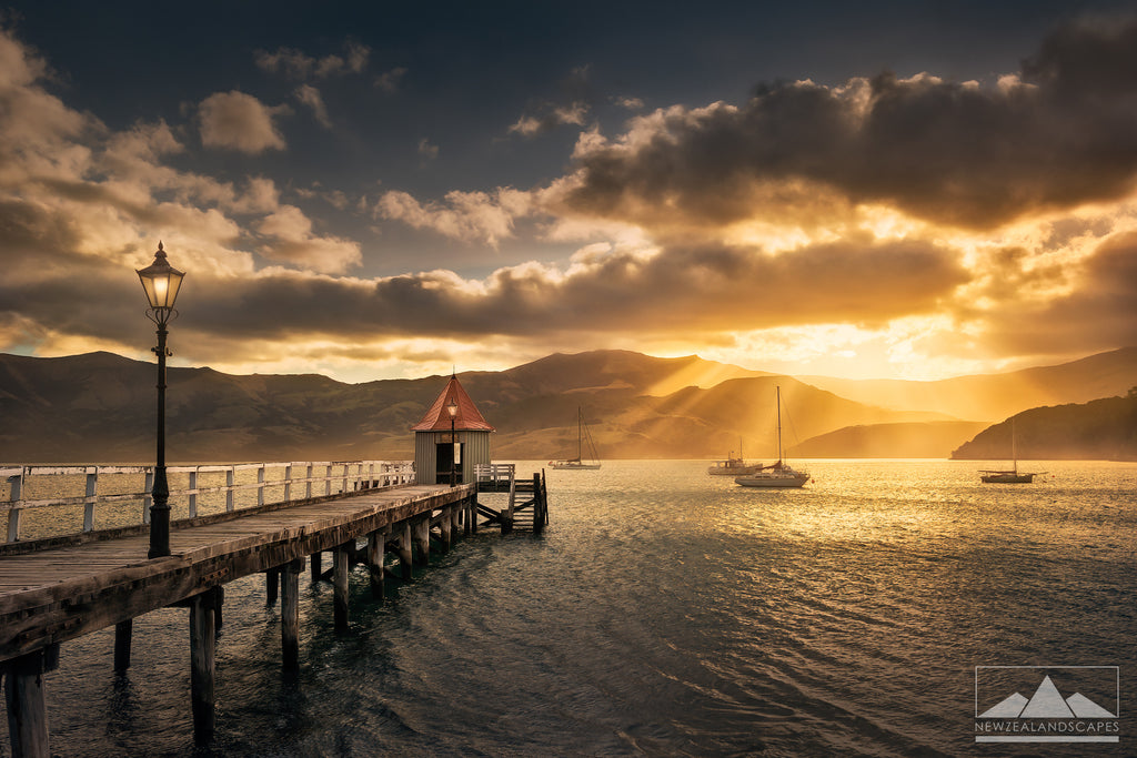Sun breaks through the cloud beyond the jetty in Akaroa Harbour