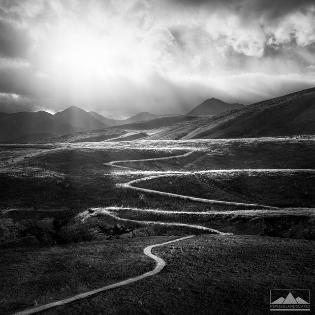 Farming path or track meandering through the New Zealand rolling hills with mountains and sunrays in the background