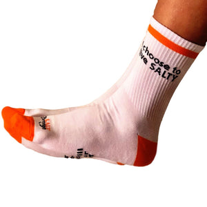 White cotton socks with orange toes and heel with slogan on the bottom and ankle salt breeze salt therapy men