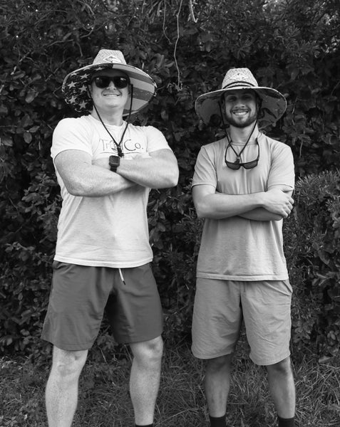 two men looking cool with sun glasses and straw hats