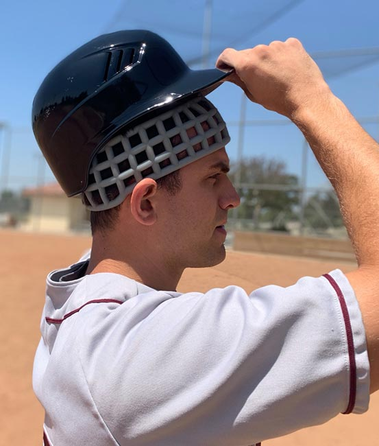 Baseball player wearing Head Net protective headgear under baseball helmet