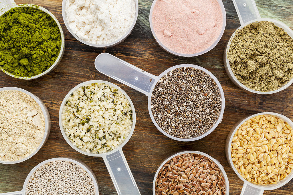Different types of protein powders in serving scoops.