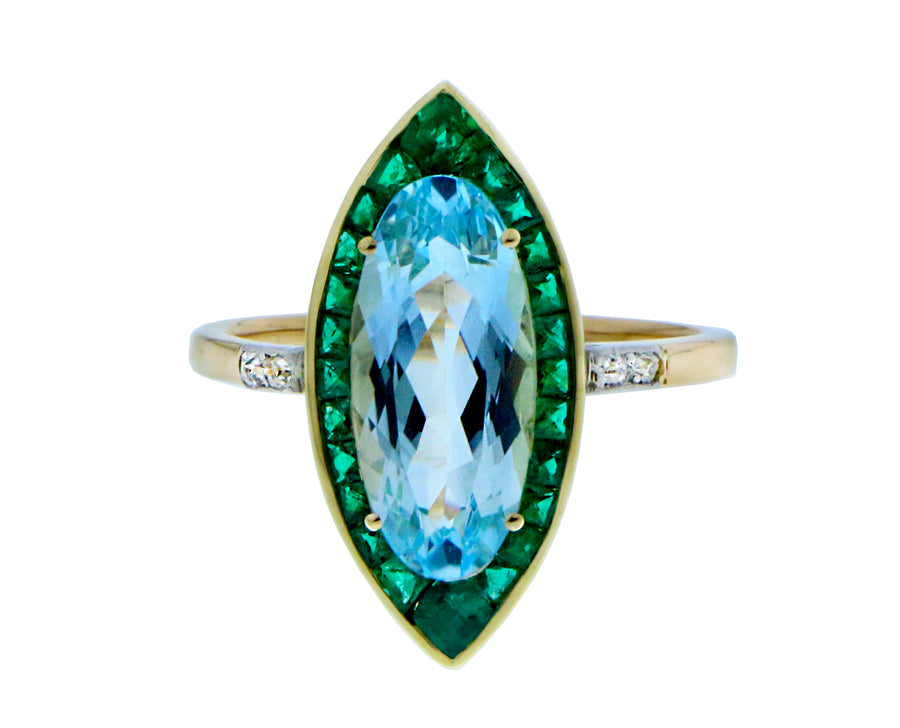 Yellow gold ring with a blue topaz, emeralds and diamonds