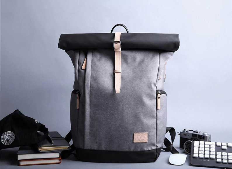 Gray Water Resistant Roll Top Backpack With USB Port on desk