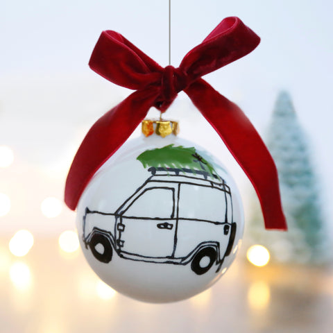 Christmas Bauble with a Land Rover Defender carrying a Christmas Tree design