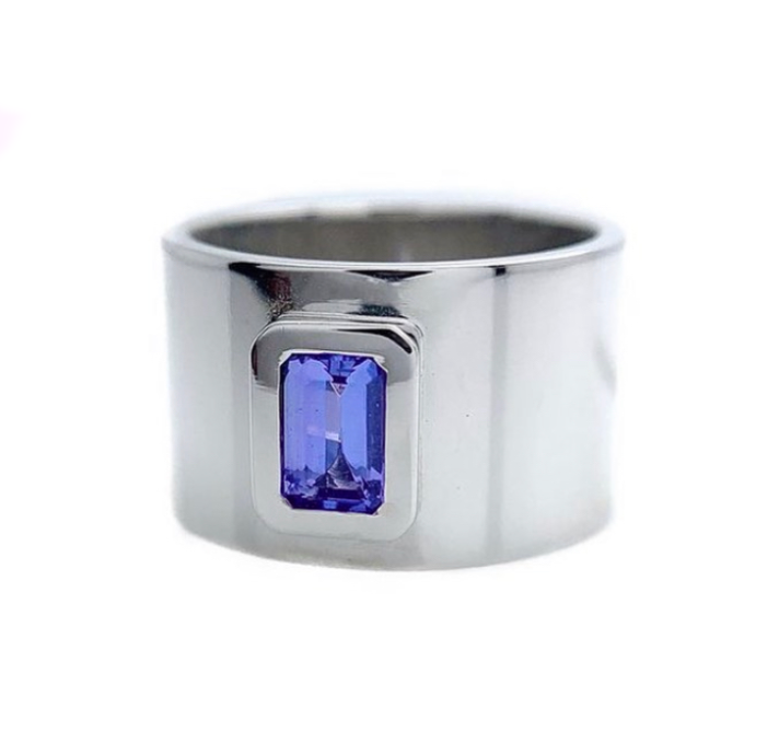 Featuring a bright, beautiful, emerald cut Tanzanite, bezel set in a wide white gold band.  Size: 6 Dimensions: 12mm wide band Stone: .056ct emerald cut Tanzanite Metal: 14k White Gold Handmade by Meg C