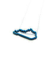 "Show your Kentucky state pride with this blue, powder-coated Kentucky outline necklace! Great paired with Meg C's Blue Kentucky State Pin.  Size: 1"" wide Metal: Blue powder coated brass; 18"" Sterling Silver chain Handmade by Meg C"