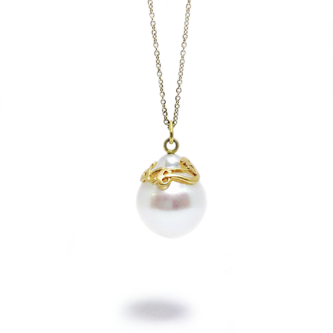 A South Sea pearl adorned with a hand-carved 18k yellow gold ribbon, with adjustable 18k yellow gold cable chain.   Size: 20mm wide; 16