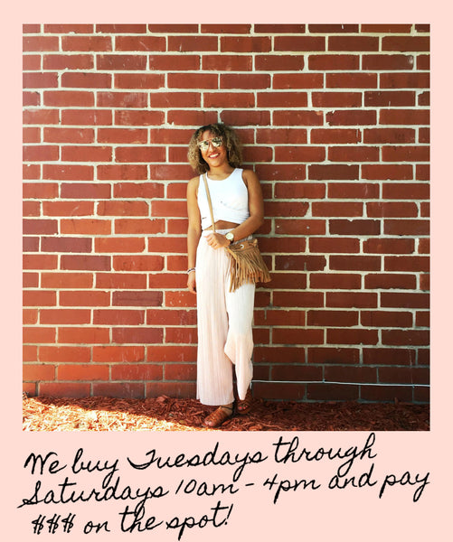 woman in front of brick wall with consignment hours
