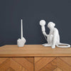 Pikkii Middle Finger Candle Holder on wooden surface next to monkey lamp
