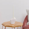 Pikkii Middle Finger Candle Holder with candle on side table next to a sofa chair