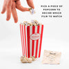 Movie Popcorn Bucket List with hand picking a scrunched paper popcorn piece
