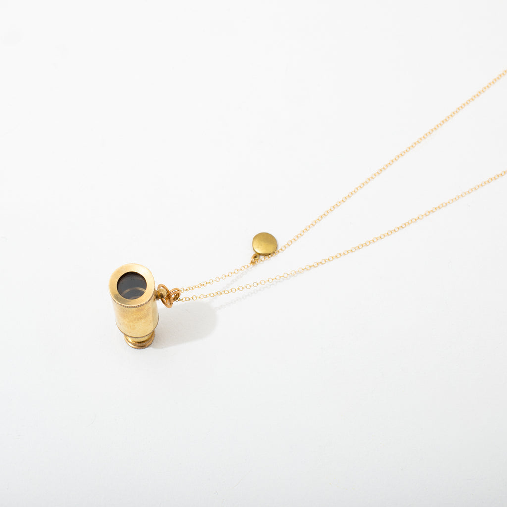 A collapsible brass telescope paired with a tiny locket hangs from shiny gold-toned brass chain. Necklace 30 inches with clasp.