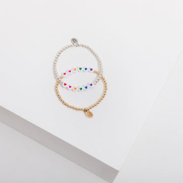Photo depicts two beaded bracelets on a white box, on is sterling silver and one is gold filled - they both have 6 white heart beads in the center with a red, a pink, a yellow, a green, a blue, and a purple heart. The bracelets are laying flat and overlapping in the center.