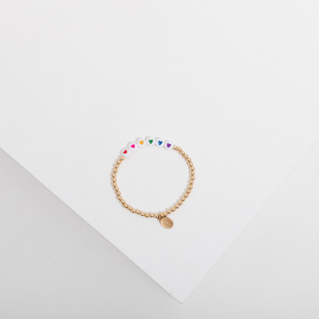 Photo depicts one gold filled beaded bracelet on a white box, the bracelet has 6 white heart beads in the center with a red, a pink, a yellow, a green, a blue, and a purple heart.