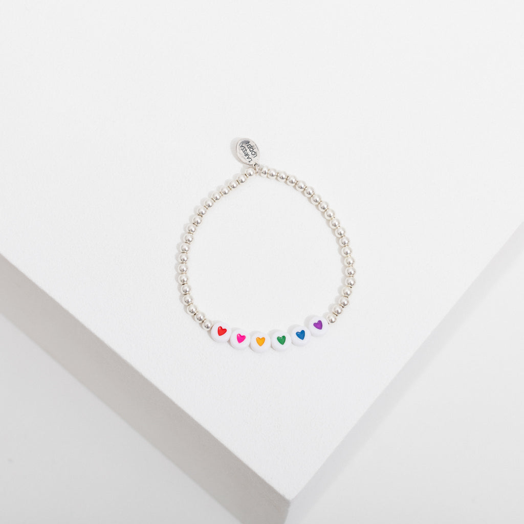 Photo depicts one sterling silver beaded bracelet on a white box, the bracelet has 6 white heart beads in the center with a red, a pink, a yellow, a green, a blue, and a purple heart.