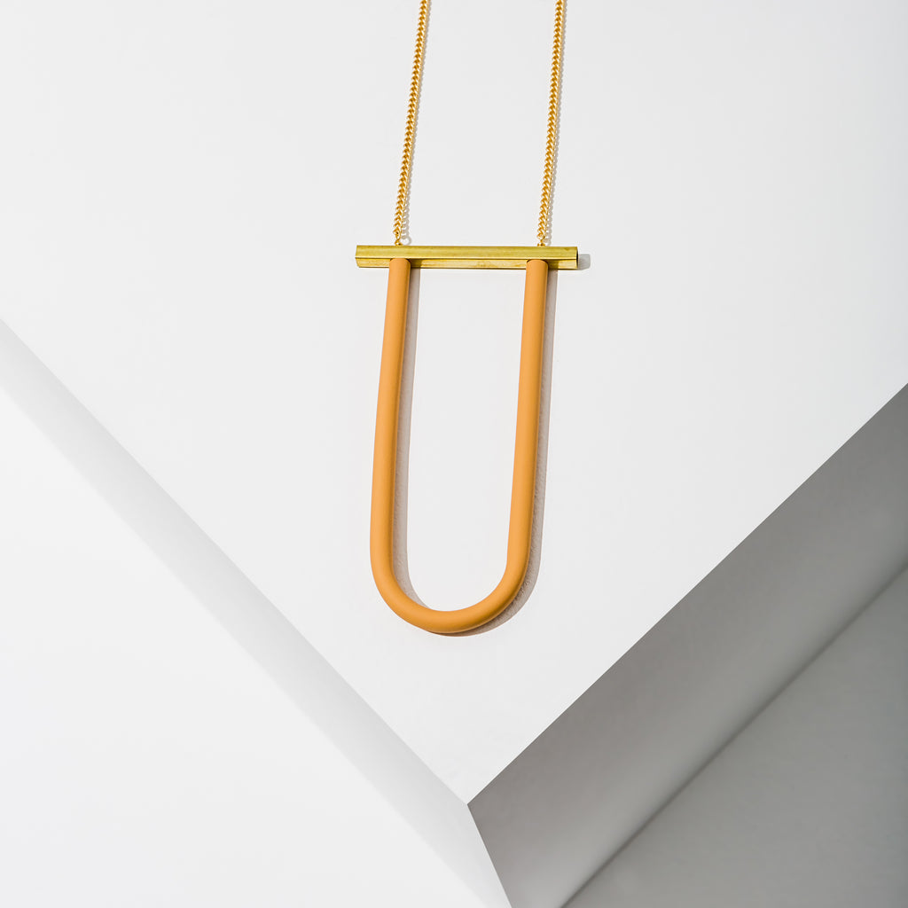 Larissa Loden Jewelry, Handmade in MN. Bauhaus Necklace, Rubberized U component wrapped to a brass bar hangs from matte gold chain. Necklace 36 inches long with no clasp.