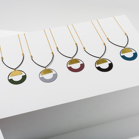 Larissa Loden Jewelry, Handmade in MN. Baltic Necklace, Rubberized brass circle accented with a brass half moon hangs from a black rubberized bar on matte gold chain. Necklace 30 inches long with no clasp.