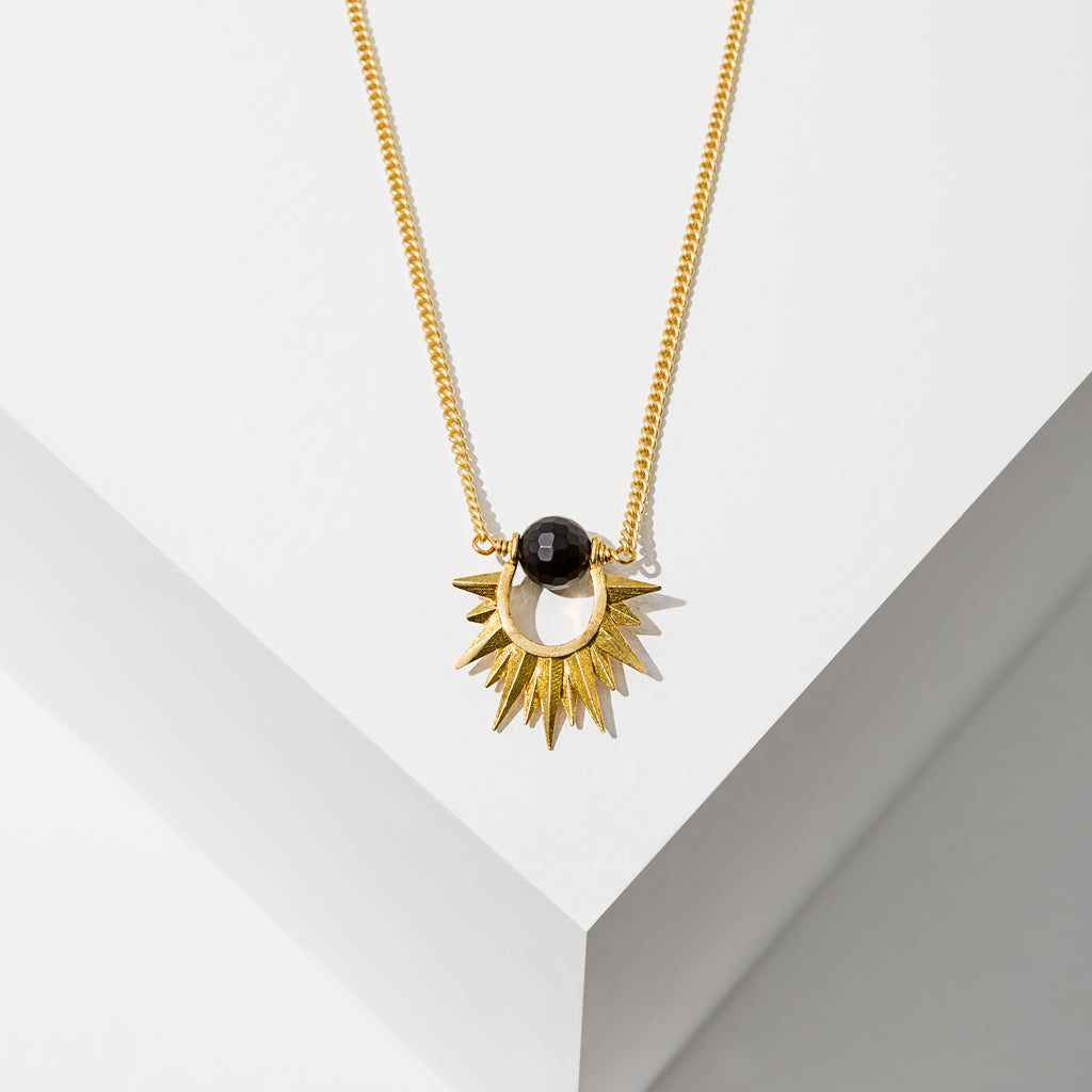 Larissa Loden Jewelry, Handmade in MN. Capri Necklace, Mini faceted gemstone wrapped around brass sun burst hangs from matte gold chain. Necklace 18 inches long with clasp.