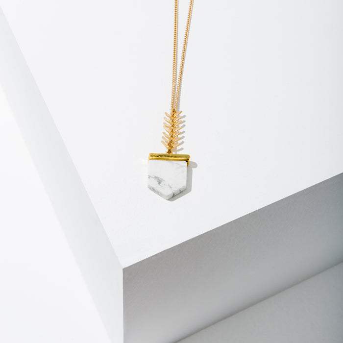 Larissa Loden Jewelry, Handmade in MN. Howlite Flat Bullet Necklace, Howlite pendant accented with spikes hang from matte gold or silver chain. Necklace 30 inches long with clasp.