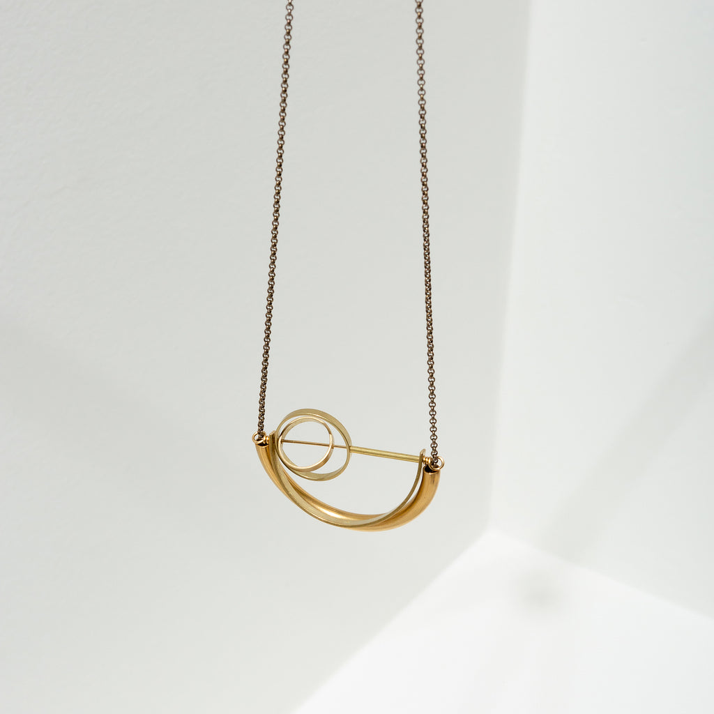 Larissa Loden Jewelry, Handmade in MN. Alden Necklace, Brass concentric circles suspended in a half circle shape on antiqued brass chain. Necklace is 30 inches long with a clasp.