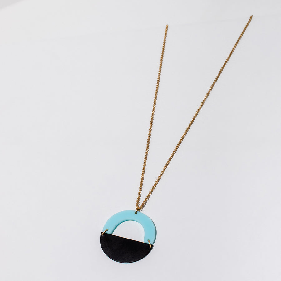 Larissa Loden Jewelry, Handmade in MN. Forme Necklace in blue, Acrylic and powder coated brass shapes in a circular pendant. Necklace is 30 inches long with a clasp.